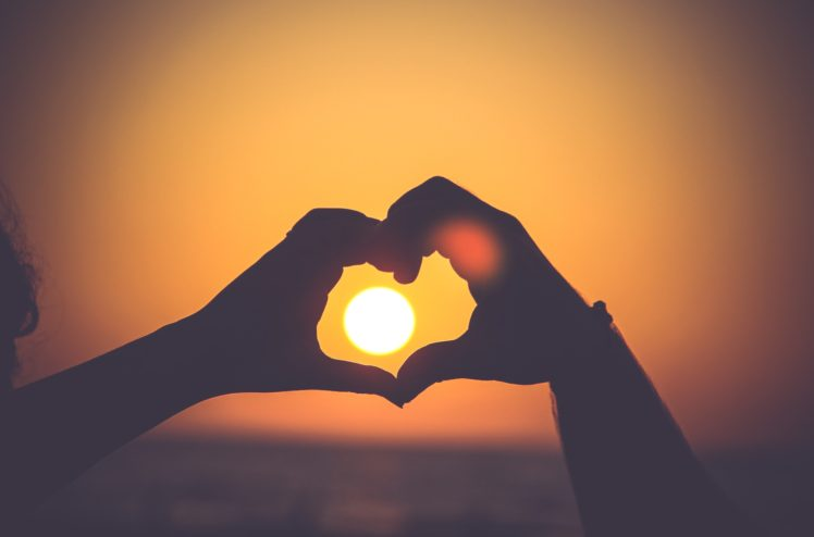 Image of hands in heart shape outlining sun in sunset