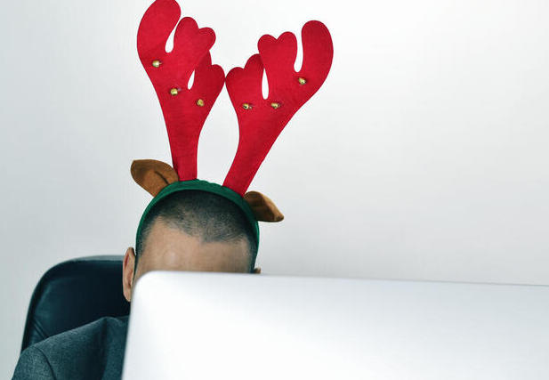 Image of man at desk wearing reindeer antlers